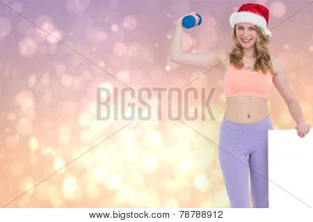 Festive fit blonde smiling at camera holding poster against pink abstract light spot design