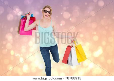 Happy blonde holding shopping bags against pink abstract light spot design