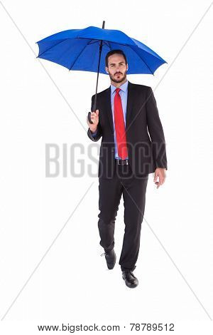 Unsmiling businessman holding an umbrella on white background