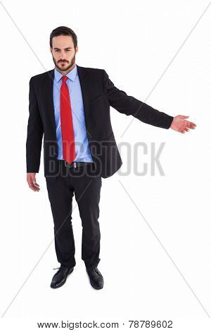 Unsmiling businessman showing something with his hand on white background