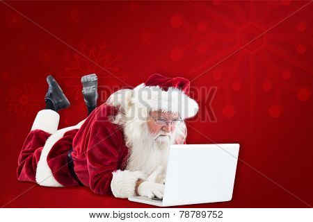Santa lies in front of his laptop against red background
