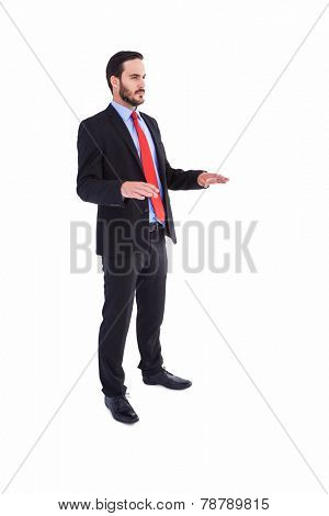 Frowning businessman presenting with hands on white background