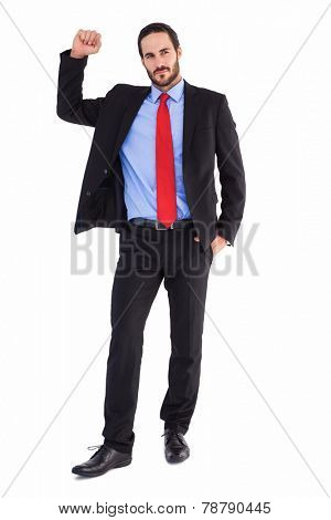 Unsmiling businessman standing with hand raised on white background