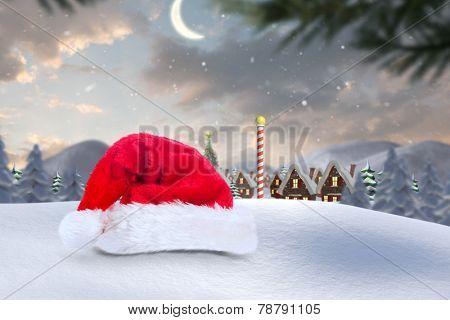 Santa hat on snow against cute christmas village at north pole