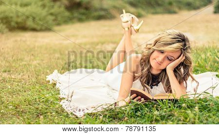 Romantic girl reading a book lying down outdoors