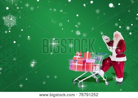 Santa pushes a shopping cart while reading against green snowflake background