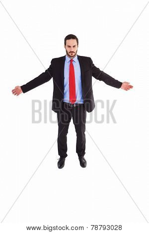 Unsmiling businessman standing with arms outstretched on white background