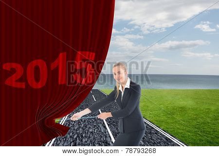 Businesswoman pulling a rope against road on grass