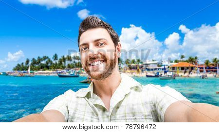 Happy young man taking a selfie photo in Porto de Galinhas, Brazil.