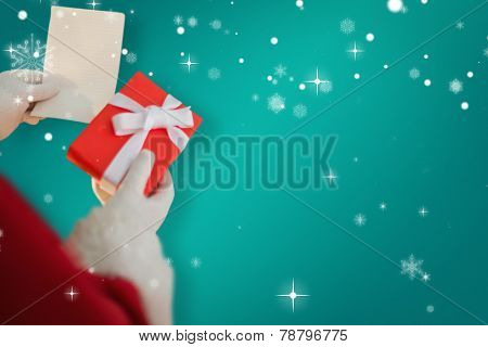 Father christmas holding a gift against green