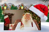 image of quaint  - Relaxed santa writing list with a quill against quaint town with bright moon - JPG