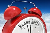 stock photo of bonnes  - Bonne annee in red alarm clock against bright blue sky over clouds - JPG