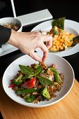 stock photo of thai food  - Food stylist grooms a dish by adding sweet basil garnish to the traditional thai dish Pad Kee Mao drunken noodle - JPG