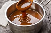 stock photo of liquid  - liquid caramel is poured into a gravy boat - JPG