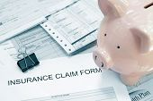 stock photo of medical  - Patient medical bills and insurance claim form with piggy bank - JPG