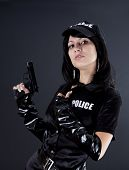picture of cap gun  - Portret of beautiful sexy policewoman with handcuffs in a black uniform that aiming a gun - JPG