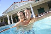 picture of 35 to 40 year olds  - Couple embracing in private swimming pool - JPG