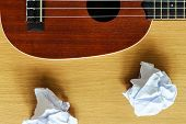 stock photo of bluegrass  - ukulele guitar with paper scraps on wood - JPG