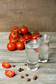 picture of ouzo  - Glasses of ouzo and tomatoes on wooden table - JPG