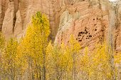 stock photo of paysage  - Dahkmar red cliffs with its troglodyte caves and trees in autumn colors - JPG