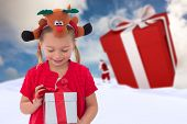 picture of rudolph  - Cute little girl wearing rudolph headband against blue sky with white clouds - JPG