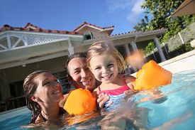 foto of bathing  - Family playing in swimming pool of private villa - JPG