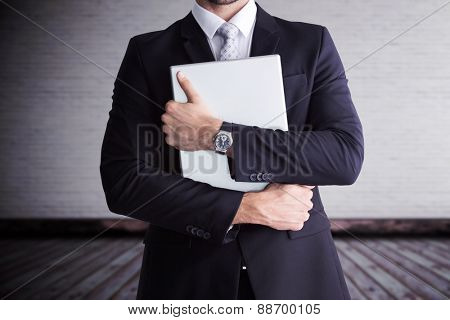 Mid section of businessman holding computer against grey room