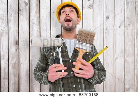 Screaming manual worker holding various tools against digitally generated grey wooden planks