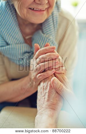 Hands of senior woman holding those of her husband