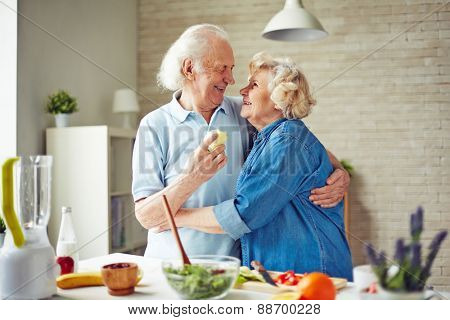Affectionate and happy seniors embracing by kitchen table