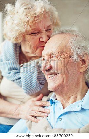 Elderly woman kissing her happy husband