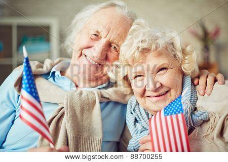 Joyful seniors with American flags looking at camera