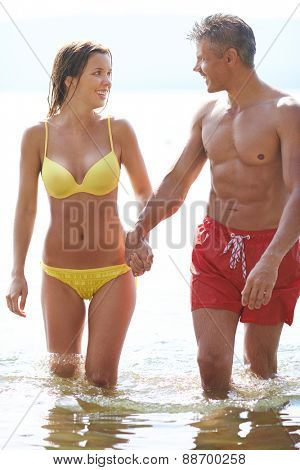 Amorous couple in swimwear walking in water