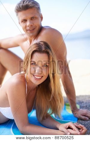Happy young couple sunbathing at summer resort