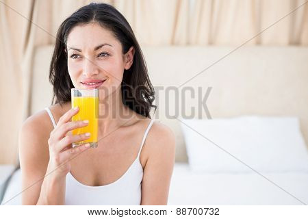 Pretty brunette holding a glass of orange juice on bed at home