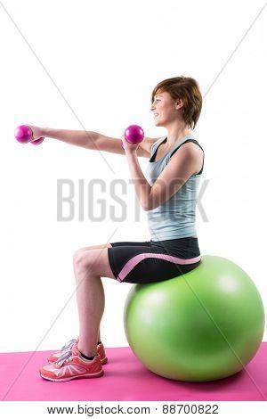 Pretty brunette exercising with dumbbells on fitness ball on white background