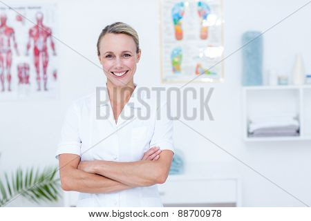 Smiling doctor looking at camera with arms crossed in medical office