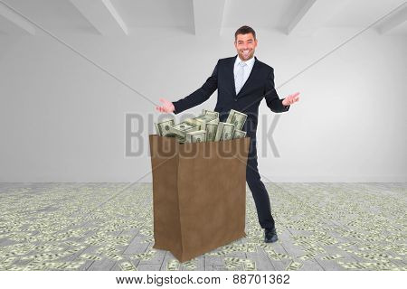 Businessman carrying bag of dollars against big room with white wall