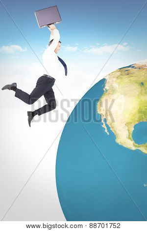 Smiling businessman leaping while briefcase against bright blue sky over clouds