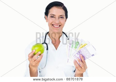 Confident female doctor holding green apple and banknotes on white background