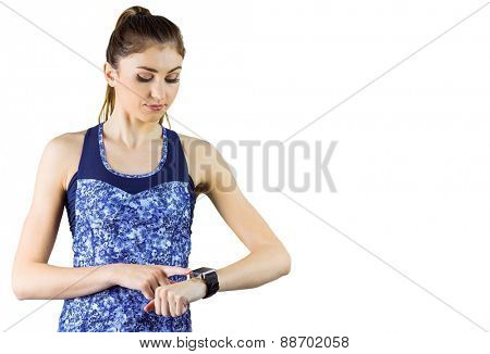 Fit brunette using her smartwatch on white background