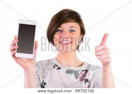 Pretty brunette holding her smartphone and looking at camera on white background
