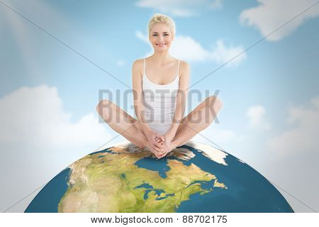 Toned young woman doing the butterfly stretch against blue sky