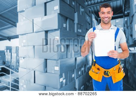 Portrait of happy repairman showing blank clipboard against shelves with boxes in warehouse