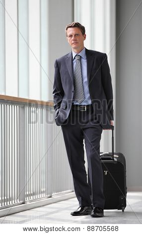 businessman travel with trolley, along the corridor