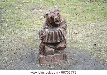 Bear (wooden one) playing button-accordion