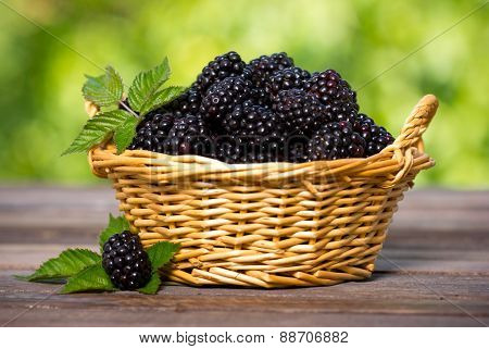 Blackberries in the basket on the wooden table