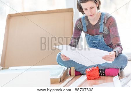Young Woman In Dungarees Reading Instructions