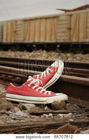 Red Shoes Leaning On The Train Tracks.