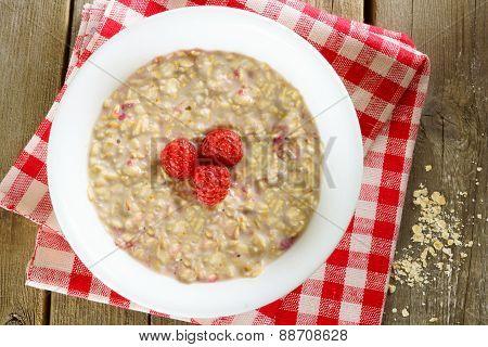 Breakfast oatmeal bowl with raspberries on cloth